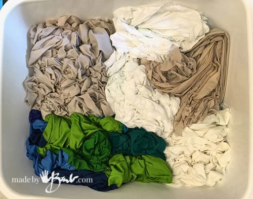various scrunched up wet fabric in plastic tub