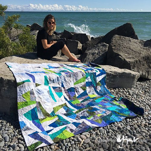 pretty girl sitting on finished quilt with blue water background