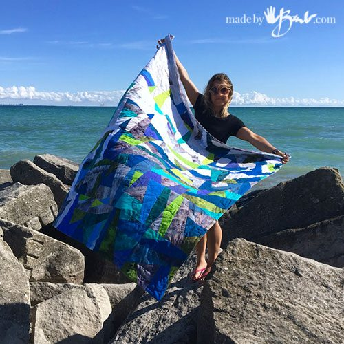girl holding blue toned quilt flying in the wind at blue beach water