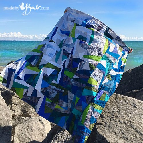 beautiful finished quilt flying in wind at beach scene