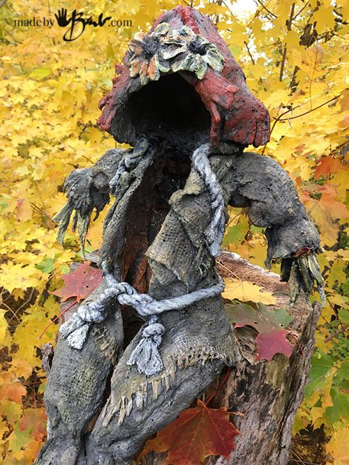 draped concrete scarecrow sitting on stump with colourful leaves in background