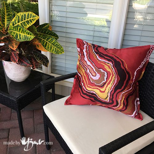 close-up of red geode design cushion on black chair