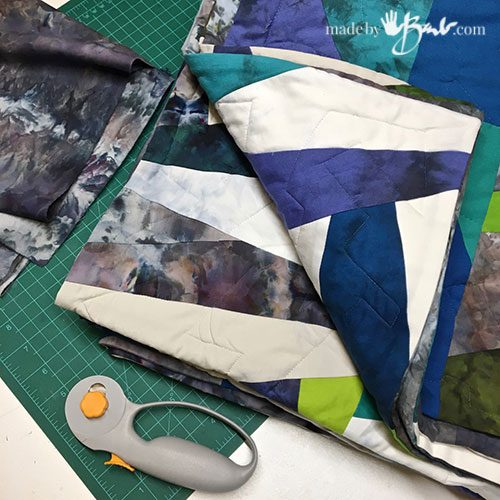 finished blue and green tone quilt with watercolour effects and rotary cutter and cutting mat