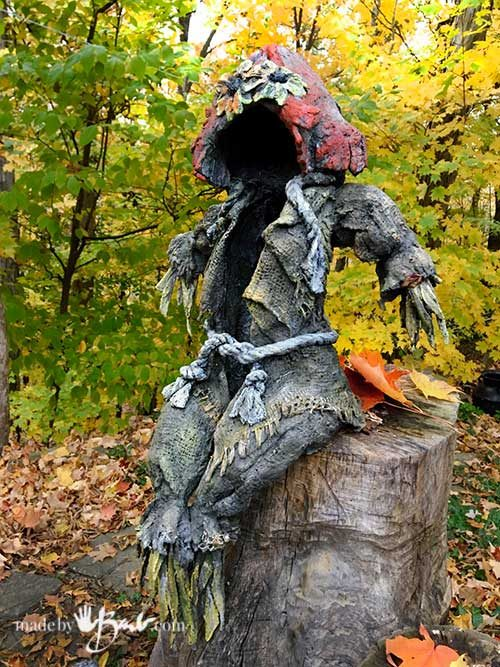 draped concrete scarecrow sitting on stump