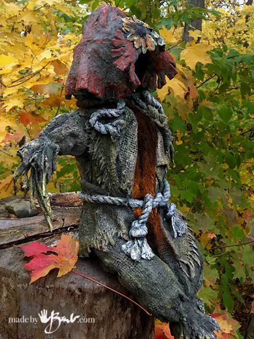 side view draped concrete scarecrow