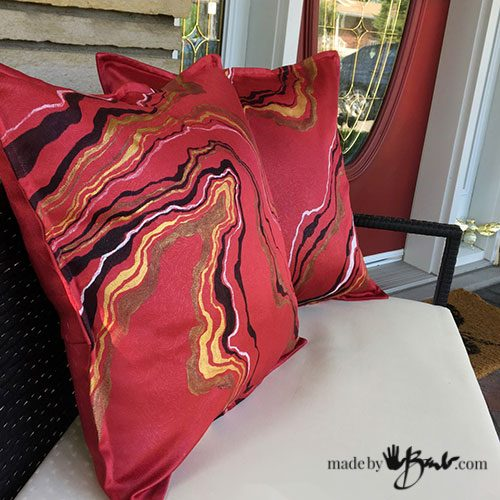 geode design pillows on patio chairs in front of red door