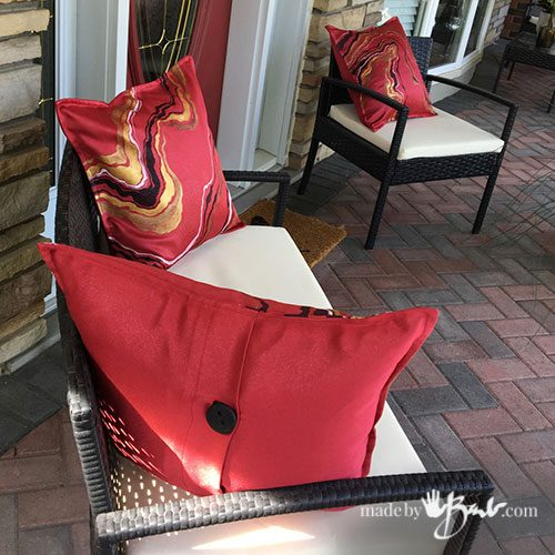 patio sofa and chair with red geode design pillows on porch