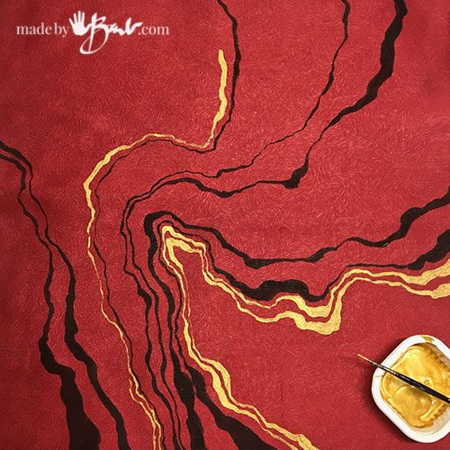 black squiggle lines painted on red fabric with gold squiggly lines added