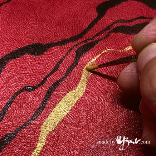 close-up of paint brushing gold onto surface of red fabric