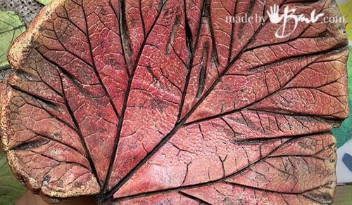 close up of red toned cast concrete leaf